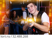 Купить «Excited guy with laser pistol while playing lasertag with his f», фото № 32488268, снято 27 августа 2018 г. (c) Яков Филимонов / Фотобанк Лори