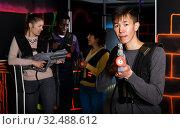Купить «Focused adult Chinese man holding laser gun», фото № 32488612, снято 23 января 2019 г. (c) Яков Филимонов / Фотобанк Лори