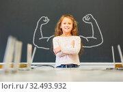 Lächelndes Mädchen in der Schule steht vor einer Tafel mit Muskeln aus Kreide. Стоковое фото, фотограф Zoonar.com/Robert Kneschke / age Fotostock / Фотобанк Лори