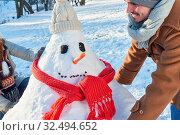 Mann baut mit seiner Familie im Winter im Garten einen Schneemann. Стоковое фото, фотограф Zoonar.com/Robert Kneschke / age Fotostock / Фотобанк Лори