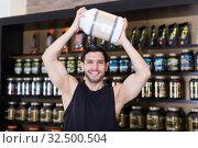 Купить «Positive bodybuilder holding sport supplements over head», фото № 32500504, снято 28 марта 2018 г. (c) Яков Филимонов / Фотобанк Лори