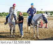 Купить «Trainer talking to woman while riding horse at farm», фото № 32500608, снято 4 июля 2018 г. (c) Яков Филимонов / Фотобанк Лори