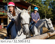 Купить «Mature couple in helmets riding by horse at barn at summer day», фото № 32500612, снято 4 июля 2018 г. (c) Яков Филимонов / Фотобанк Лори