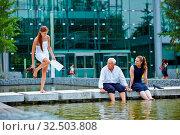 Business Team kühlt Füße im Wasser von einem Teich vor dem Büro. Стоковое фото, фотограф Zoonar.com/Robert Kneschke / age Fotostock / Фотобанк Лори
