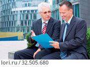 Zwei Geschäftspartner reden im Freien über eine Akte. Стоковое фото, фотограф Zoonar.com/Robert Kneschke / age Fotostock / Фотобанк Лори