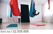 Купить «Aerial yoga - two women doing a spin and getting in the hammock», видеоролик № 32508808, снято 27 мая 2020 г. (c) Константин Шишкин / Фотобанк Лори