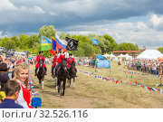 Купить «Russia, Samara, July 2019: Solemn entry of a group of horse racing with flags in the meadow of the festival.», фото № 32526116, снято 28 июля 2019 г. (c) Акиньшин Владимир / Фотобанк Лори