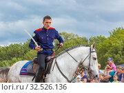 Russia, Samara, July 2019: Cossack performs stunts on a galloping horse. Редакционное фото, фотограф Акиньшин Владимир / Фотобанк Лори