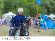Купить «Russia, Samara, July 2019: Young Cossack performs stunts on a galloping horse.», фото № 32526140, снято 28 июля 2019 г. (c) Акиньшин Владимир / Фотобанк Лори