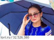 Купить «Russia, Samara, July 2019: Ethnic festival. Kazakh girl in national dress under an umbrella.», фото № 32526380, снято 28 июля 2019 г. (c) Акиньшин Владимир / Фотобанк Лори
