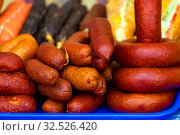 One of the varieties of cooked smoked sausages. Loafs of delicious Krakow sausage lie on a blue tray. Стоковое фото, фотограф Акиньшин Владимир / Фотобанк Лори