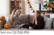 Купить «girls in halloween costumes with candies at home», видеоролик № 32526956, снято 14 ноября 2019 г. (c) Syda Productions / Фотобанк Лори