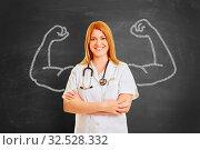 Starke Ärztin steht vor Tafel mit Muskeln aus Kreide. Стоковое фото, фотограф Zoonar.com/Robert Kneschke / age Fotostock / Фотобанк Лори