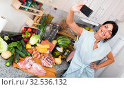Купить «Female is taking selfie by phone near purchases that she buying», фото № 32536132, снято 5 сентября 2017 г. (c) Яков Филимонов / Фотобанк Лори