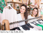 Купить «Smiling female friends choosing sweater in the modern shop», фото № 32536416, снято 15 марта 2018 г. (c) Яков Филимонов / Фотобанк Лори