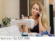 Купить «Woman at the sewing machine talking on the phone», фото № 32537040, снято 29 ноября 2019 г. (c) Евгений Харитонов / Фотобанк Лори