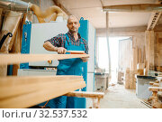 Carpenter processes board on plane machine. Стоковое фото, фотограф Tryapitsyn Sergiy / Фотобанк Лори