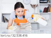 Купить «Young woman in uniform cleaning table with spray in office», фото № 32538416, снято 18 апреля 2018 г. (c) Яков Филимонов / Фотобанк Лори