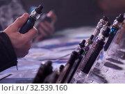 Мужчина выбирает электронные сигареты, которые стоят на прилавке в магазине города Москвы, Россия (2019 год). Редакционное фото, фотограф Николай Винокуров / Фотобанк Лори
