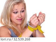 Eine junge Frau mit einem Maßband vor der nächsten Diät. Abnehmen und fasten. Стоковое фото, фотограф Zoonar.com/Erwin Wodicka / age Fotostock / Фотобанк Лори