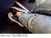 Купить «Female passenger stretching her legs on long commercial airplane flight. Exit seats with more leg space for more comfortable flight. Focus on fashionable jeans tear.», фото № 32542532, снято 3 июня 2020 г. (c) easy Fotostock / Фотобанк Лори