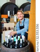 Купить «Man seller wearing apron having package box with wine bottles», фото № 32553556, снято 6 июня 2020 г. (c) Яков Филимонов / Фотобанк Лори