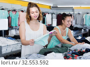 Купить «Young women friends selecting new pants in store», фото № 32553592, снято 19 июня 2017 г. (c) Яков Филимонов / Фотобанк Лори
