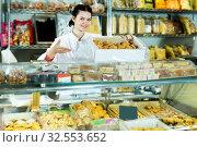 Купить «Seller in white uniform with dark cookies», фото № 32553652, снято 22 марта 2017 г. (c) Яков Филимонов / Фотобанк Лори