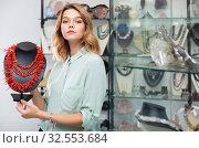 Купить «Saleswoman demonstrating red coral necklace», фото № 32553684, снято 11 июля 2020 г. (c) Яков Филимонов / Фотобанк Лори