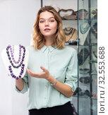 Купить «Saleswoman offering amethyst necklaces», фото № 32553688, снято 21 февраля 2020 г. (c) Яков Филимонов / Фотобанк Лори