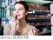 Купить «female customer looking for lipstick in cosmetics shop», фото № 32553728, снято 21 февраля 2017 г. (c) Яков Филимонов / Фотобанк Лори