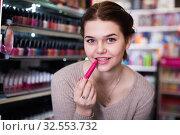 Купить «Smiling female looking for make-up items», фото № 32553732, снято 21 февраля 2017 г. (c) Яков Филимонов / Фотобанк Лори