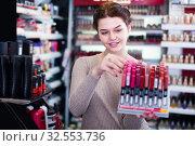 Купить «joyous woman customer deciding on make-up items in cosmetics shop», фото № 32553736, снято 21 февраля 2017 г. (c) Яков Филимонов / Фотобанк Лори