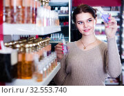 Купить «Young girl customer is searching for strong perfume», фото № 32553740, снято 21 февраля 2017 г. (c) Яков Филимонов / Фотобанк Лори
