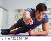 Купить «Young man exercising at home in sports and healthy lifestyle con», фото № 32554436, снято 3 мая 2017 г. (c) Elnur / Фотобанк Лори