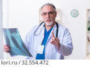 Купить «Old male doctor working in the clinic», фото № 32554472, снято 15 марта 2019 г. (c) Elnur / Фотобанк Лори