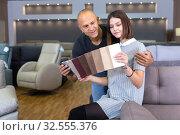 Купить «Couple choosing upholstery fabric in salon», фото № 32555376, снято 29 октября 2018 г. (c) Яков Филимонов / Фотобанк Лори