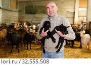 Купить «Positive farmer with goatlings on his hands», фото № 32555508, снято 15 декабря 2018 г. (c) Яков Филимонов / Фотобанк Лори