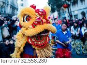 Купить «Paris, France - Feb 02, 2014: Chinese performers dance with a dragon at the chinese lunar new year parade.», фото № 32558280, снято 2 февраля 2014 г. (c) age Fotostock / Фотобанк Лори