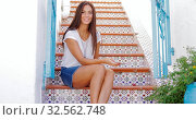 Купить «Attractive young woman in casual outfit traveling and posing on colorful street stairs sitting with smarpthone and looking happily at camera.», фото № 32562748, снято 30 мая 2020 г. (c) easy Fotostock / Фотобанк Лори
