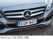 Finnish licence plate is on front of Mercedes-Benz car. It is European type plate with blue sign of EU and FIN inscription on side of shield (2019 год). Редакционное фото, фотограф Кекяляйнен Андрей / Фотобанк Лори