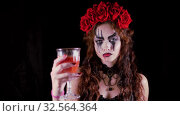 Easy Halloween Makeup. The girl with the picture on her face. The devil's bride with a wreath of red flowers on her head. Woman drinks from a glass of red drink offering to drink to the viewer. Стоковое видео, видеограф Константин Мерцалов / Фотобанк Лори