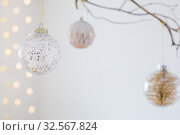 Купить «Christmas balls on golden branch in white interior», фото № 32567824, снято 2 декабря 2019 г. (c) Майя Крученкова / Фотобанк Лори