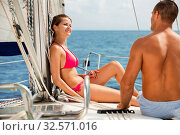 Купить «Smiling young couple talking while sitting on deck of their sailboat enjoying sea trip on sunny summer day», фото № 32571016, снято 5 декабря 2019 г. (c) Яков Филимонов / Фотобанк Лори