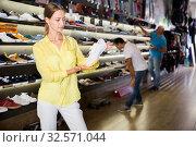 Young positive woman shopping casual sneakers in modern store. Стоковое фото, фотограф Яков Филимонов / Фотобанк Лори