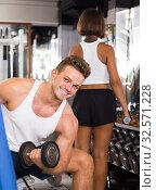 Купить «smiling man making biceps curls in gym», фото № 32571228, снято 4 октября 2016 г. (c) Яков Филимонов / Фотобанк Лори