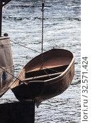 Metallic boat hangs over water on steel chain overboard (2019 год). Стоковое фото, фотограф Олег Елагин / Фотобанк Лори