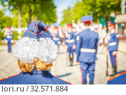 Russia, Samara, June 2017: white bows from a girl in a cadet at demonstration shows on the Volga embankment on a sunny summer day. Редакционное фото, фотограф Акиньшин Владимир / Фотобанк Лори