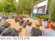 "Купить «Russia, Samara, July 2017: young people listen to a lecture on the embankment at the festival ""Volgafest"" on a summer day. Text in Russian: today the factories are turning into lofts.», фото № 32572016, снято 11 июня 2017 г. (c) Акиньшин Владимир / Фотобанк Лори"