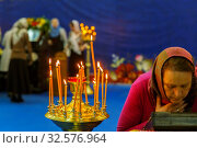 Купить «Russia, Samara, April 2017: a believing woman performs the worship of the ark with a part of the relics of St. Seraphim of Sarov. Burning candles in standing in a candlestick. Text in Russian: samara.», фото № 32576964, снято 21 апреля 2017 г. (c) Акиньшин Владимир / Фотобанк Лори
